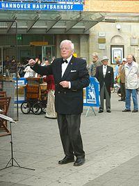 2014-06-27 Ernst Müller dirigiert das Niedersächsische Blasorchester vor dem Hauptbahnhof Hannover, Ernst-August-Denkmal, Ernst-August-Platz.jpg