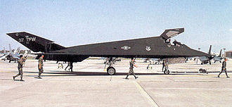 37th Training Wing - F-117A Nighthawk 85-0830 being towed at Tonopah after its return from Operation Desert Storm, 1991. Note the spotters, the armed security police with M-16s, and tow bar attached to the front landing gear.