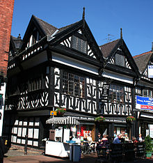A black-and-white building in a corner position, with two gables to the front and one visible to the left side. On the street in front is a pavement café.