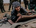 A YPJ fighter prepares her rifle for firing.jpg