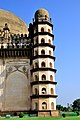 A partial view of the huge Gol Gumbaz and one of the four dome-capped octagonal tower seven stories high with a staircase inside. Vijayapura (Bijapur), Karnataka.jpg