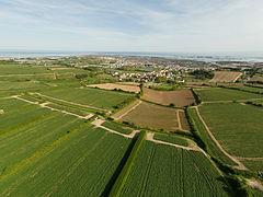 Zdjęcie przedstawia widok z powietrza na pola uprawne i znajdujące się nieopodal nich zabudowania miasteczka Saint Clement. W tle, za miasteczkiem widoczna jest plaża i skały na brzegu morza.