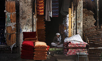 An Afghan man reads outside his market shop wh...