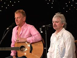 Two man standing at microphones, both are shown facing slightly to the right. Male at left has a guitar and is resting his left arm over it. The second male is shorter and has a moustache.