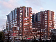 A red, four-story building with two eight-story towers rising above it