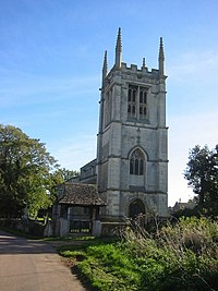 The tower of a stone church, seen from the west, at the top of which is a battlemented parapet with pinnacles.  In front of the church and to the left is a lychgate