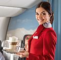 An Austrian Airlines flight attendant serving refreshments to passengers (cropped).jpg