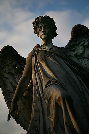 An angel spreads his wing on a tomb at Cimitero Monumentale in Milan