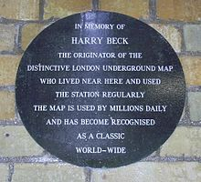 "A circular plaque on a brick wall with the words: ""In memory of Harry Beck the originate of the distinctive London Underground map who lived near here and used the station regularly. The map is used by millions daily and has become recognised as a classic world-wide."""