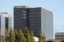 Un bâtiment moderne, sombre, avec une façade en verre