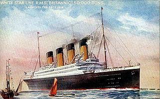 Navio a vapor mostrado no mar, com fumaça saindo de três dos seus quatro pilhas, e dois veleiros em primeiro plano.  O navio está em sua maioria negros, pintados de branco e acima dos pavimentos descobertos.