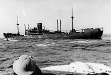 A dark-coloured merchant ship at sea. The head of a person wearing a sun helmet is visible in the foreground