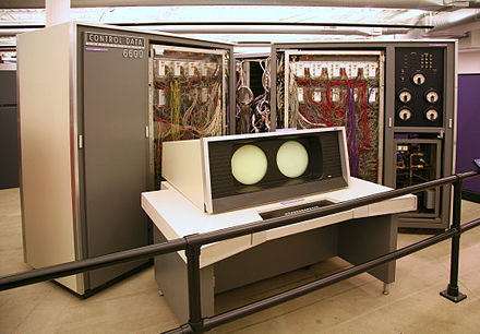 "The CDC 6600. Behind the system console are two of the ""arms"" of the plus-sign shaped cabinet with the covers opened. Each arm of the machine had up to four such racks. On the right is the cooling system. CDC 6600.jc.jpg"