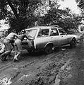 COLLECTIE TROPENMUSEUM Het aanduwen van een auto die door de modder op de weg dreigt weg te slippen TMnr 20010530.jpg