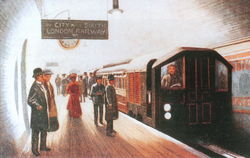 A train pulled by a driving motor car arrives at a station with the driver in view at the controls. Passengers waiting on the platform in Edwardian dress cast long shadows in the brightly lit station.