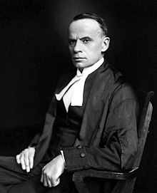 A dark-haired middle-aged man sits in a wooden chair, facing left. He is wearing judicial robes.
