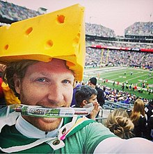 A man wearing a green Packers jersey and a large wedge of fake cheese on his head