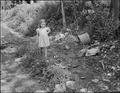 Child of miner walks down the road. This is all the street there is, there are no garbage collections and trash and... - NARA - 541041.tif