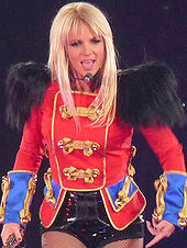 A woman with blond hair, wearing a blue, red, and black outfit.
