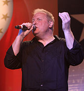 A blond-haired man wearing a black shirt, singing into a microphone
