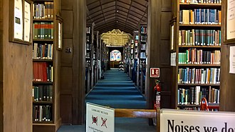 Corpus Christi College, Oxford - The aisle of the library as seen from the former President's Study in the far west end. The chapel is visible through a pane of glass at the end of the library.