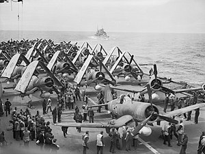 Black and white photo of a large number of single engined monoplane aircraft on the deck of an aircraft carrier at sea. Another ship is visible in the background.