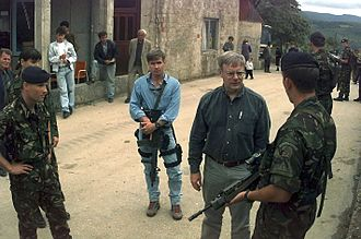 Bodyguard - Walter B. Slocombe, the U.S. Under Secretary of Defense for Policy with his bodyguard in Bosnia and Herzegovina in 1996. The bodyguard is armed with an M-16, a 5.56 mm, magazine-fed, select-fire rifle.