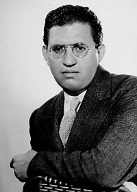 head shot of a well-dressed man wearing glasses