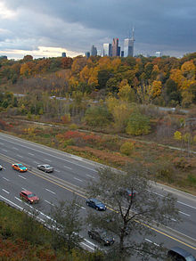 A photo of a freeway in a ravine in the autumn, taken from atop the edge of the ravine. Projecting above the forest is the top of several skyscrapers and the CN Tower.