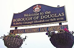 A large sign greeting people to Douglas in two languages