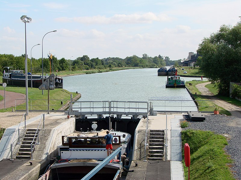 The canal lock on the Canal latéral à l'Aisne in Berry-au-Bac, with a canal boat inside.To the right, the mound of the Canal de l'Aisne à la Marne