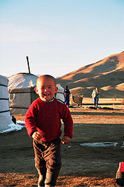 A young Mongolian boy in front of a yurt in the countryside
