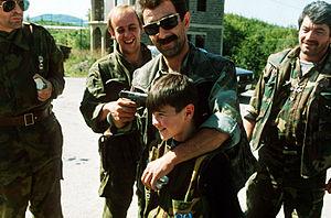 English: A Serb commander puts a gun to the he...