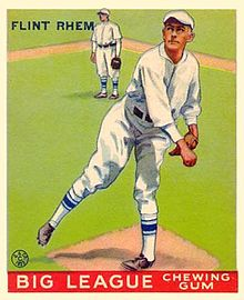 A baseball card of a man wearing a white baseball uniform with blue trim standing on a pitcher's mound after throwing a ball.