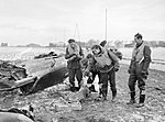 Four pilots of No. 92 Squadron RAF based at Manston, Kent, pick through the wreckage of a Junkers Ju 87B, which they shot down while it was attempting to attack a convoy in the English Channel on 5 February 194 CH2065.jpg