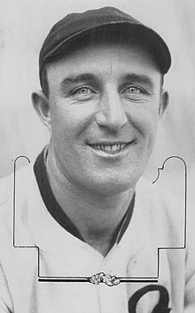 A close-up of a smiling man wearing a light-colored baseball jersey and a dark cap looking into the camera.