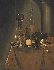 A roemer filled with wine and a lemon on a silver charger, an upturned tazza, a wine flute with a lid, grapes, a partly-peeled lemon and a knife on a draped table in an interior