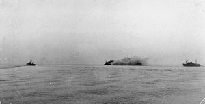 HMS Nigeria (60) - A distant view of Nigeria stopped and on fire after being torpedoed