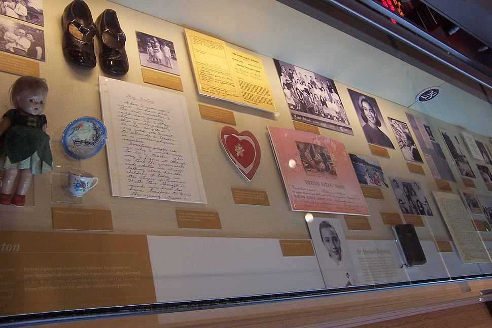 Museum display case containing photographs, papers, shoes, doll, and other early childhood artifacts of Hillary Rodham's early life