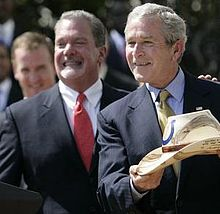 Irsay smiling next to Bush, holding a Stetson hat with a Cowboys logo on it