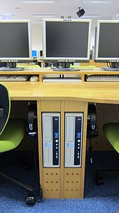A close-up of the space between two student terminals. There are two computers embedded into the desk, and flat-screen monitors sit on top of the desk. The students' headphones are hanging on hooks below the desk.