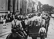 A black-and-white photo showing Japanese troops, some on horsebacks, entering Saigon.