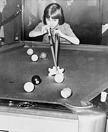 Young girl using a bridge to take a shot on a pool table