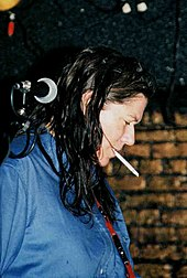 Kim Deal standing next to a microphone