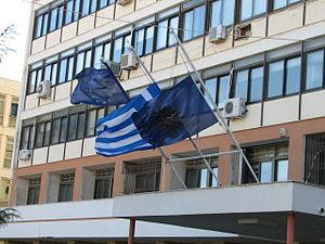 Flag of Macedonia (Greece) - Vergina Sun flag at the Kozani Prefecture, along with the European flag and the flag of Greece.