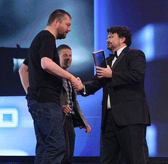 """Limbo (video game) - Arnt Jensen, game director of Playdead (left) and artist Morten Bramsen (back) receive the """"Best Visual Art"""" award for Limbo from Tim Schafer at the 2011 Game Developers Choice Awards"""