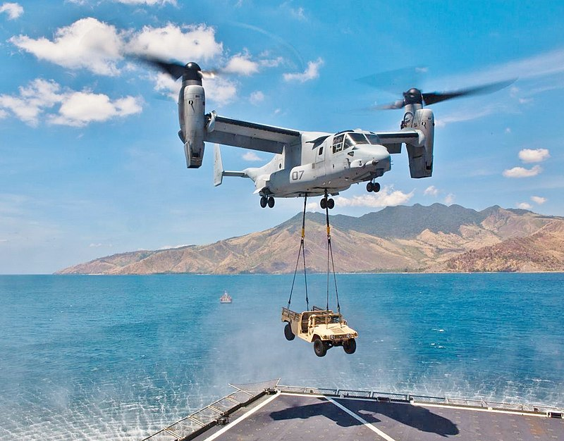 A MV-22 Osprey with its rotors up to vertical with a HMMWV vehicle hanging by two sling wires.