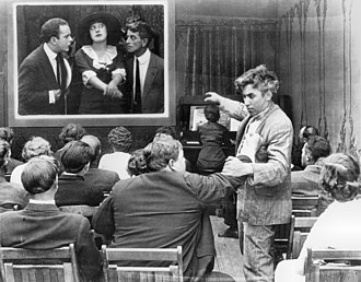 Mack Sennett - Movie theatre audience members Roscoe Arbuckle and Mack Sennett square off while watching Mabel Normand onscreen in Mabel's Dramatic Career (1913)