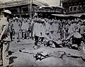 Man being beheaded in China, while the body of a man already executed lays in the street with three westerners in the crowd.jpg