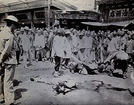 A Boxer is publicly executed. Man being beheaded in China, while the body of a man already executed lays in the street with three westerners in the crowd.jpg